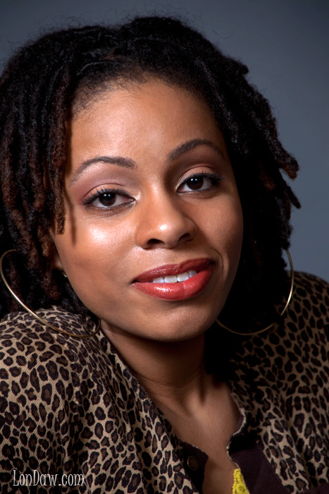 woman in brown leopard pattern with dreds and hoop earrings