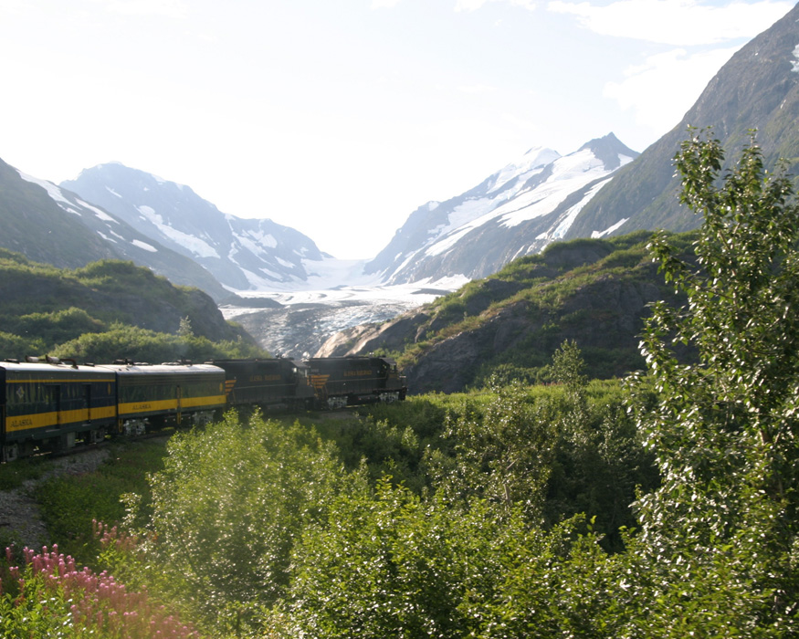 Train passing fields with of glaciers in Alaska