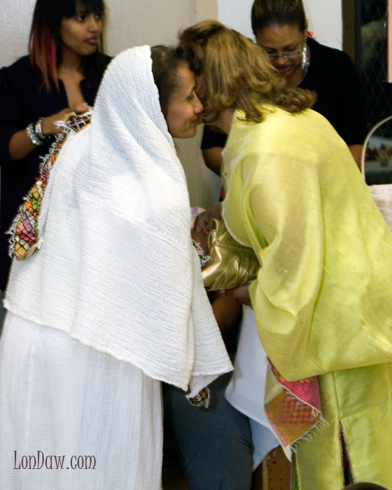 Women warmly greet each other at Ethiopian Engagement Party