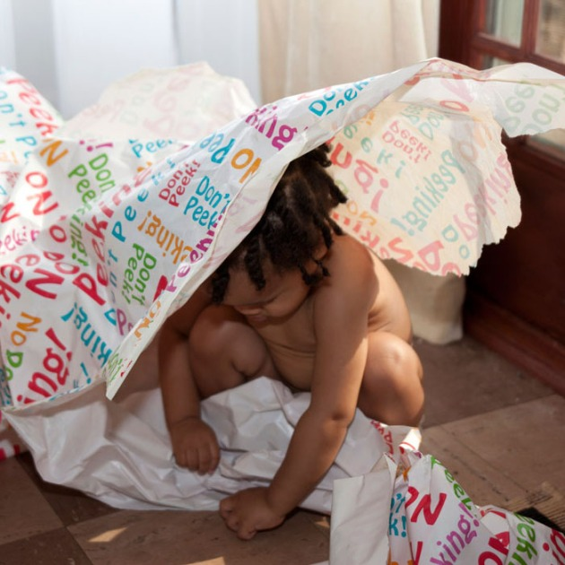 toddler playing with unrolled giftwrap paper