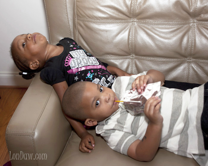 Boy and girl playfully lying on couch