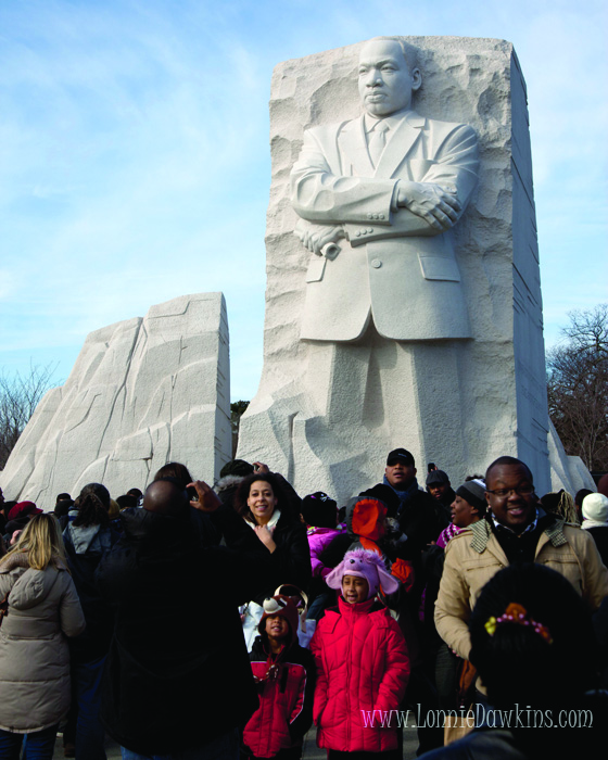 Statue of Martin Luther King stands above crowd at National Memorial