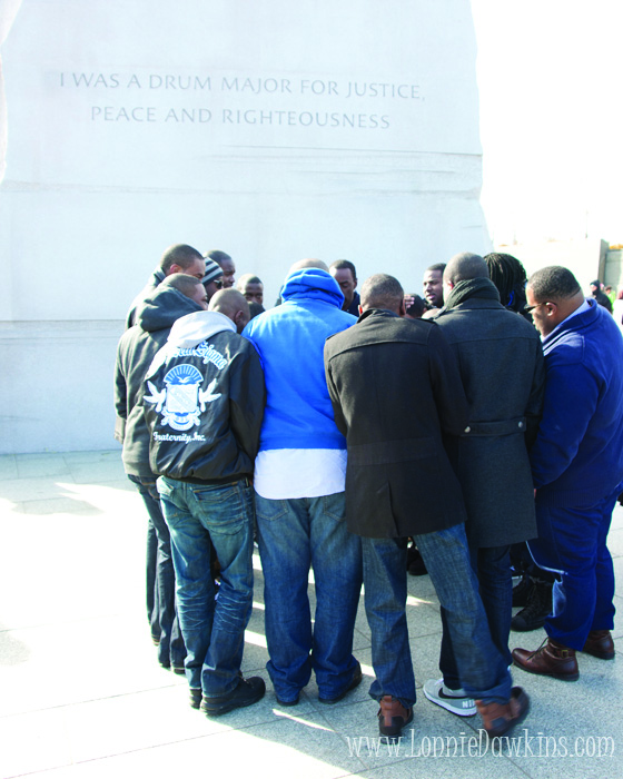 Fraternity gathered in huddle in front of Stone of Hope at King National Memorial