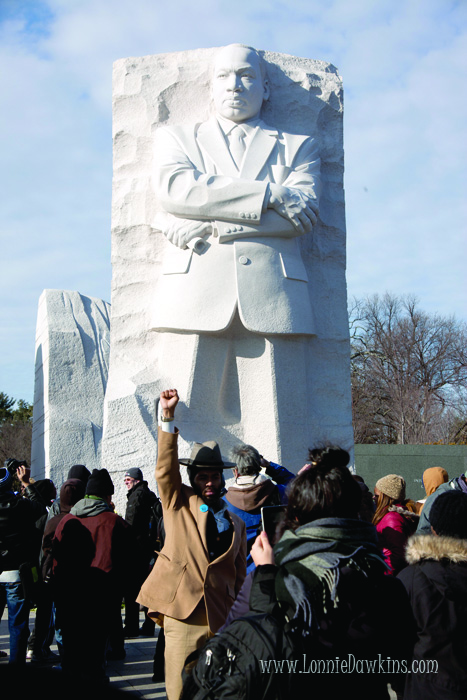 Man in brown suit and hat poses with raised fist at Martin Luther King Memorial