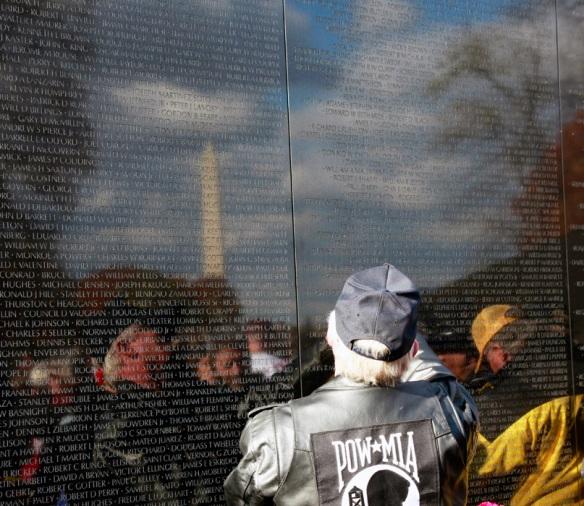 Visitors at Veterans Memorial wall tracing names