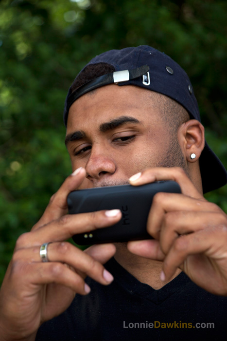young male outdoors using camera phone