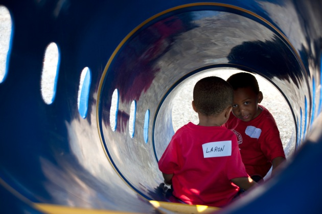 boys going down the tube slide at the playground