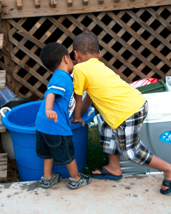 Two boys fascinated by ice in large bucket