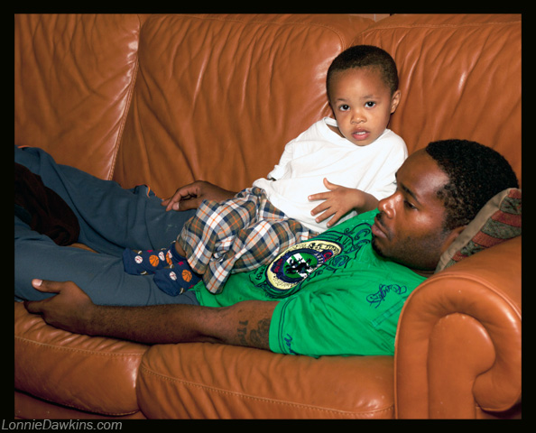 Father and son relaxing on sofa