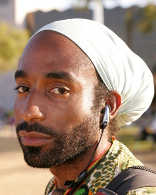 man with ear plugs and white turban head covering