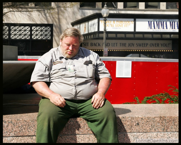 man asleep in front of National theater with funny sign