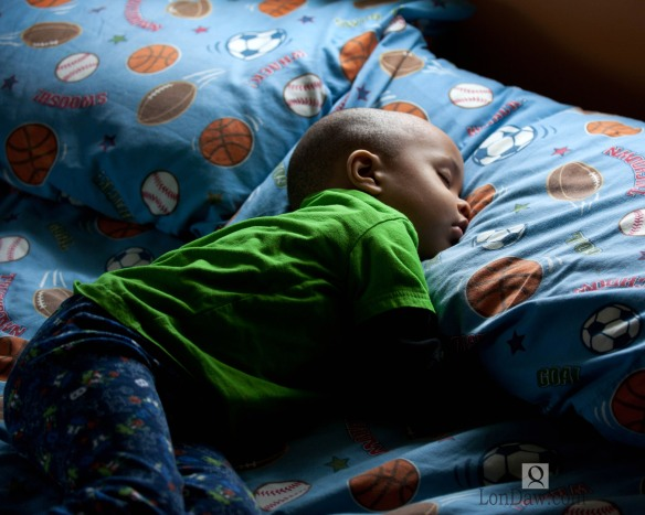 image of young African american boy asleep in bed in pajamas with sunlight.