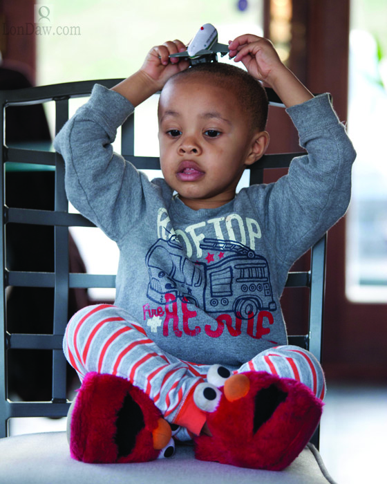 Young African American boy with Elmo Slippers and toy airplane playing in chair