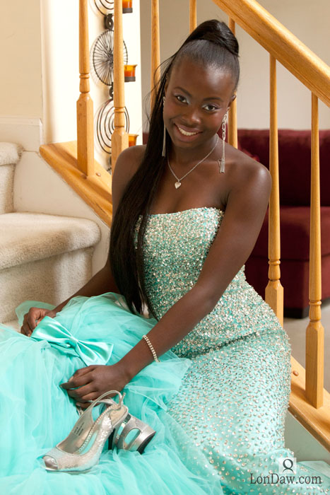 young African American woman wearing beautiful gown sitting on stairs