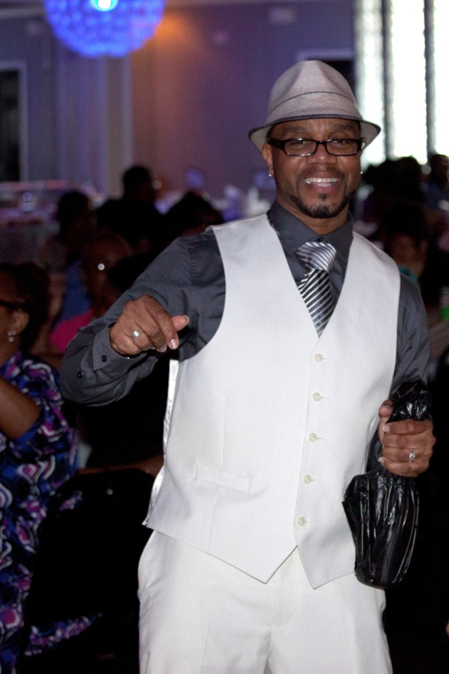 man in white suit dancing at his birthday party