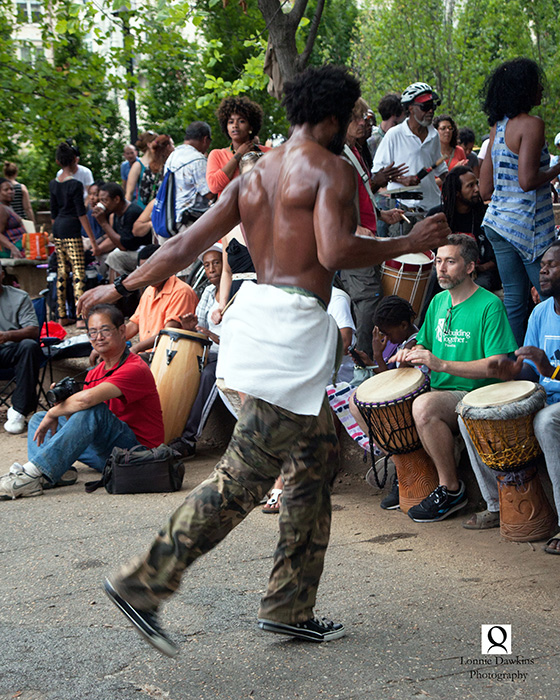 5b-Shirtless black male dancing to beat of drummers in park