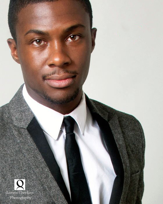 Young African American man in grey suit and black tie