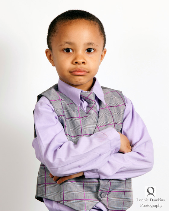 young boy in vest arms crossed purple