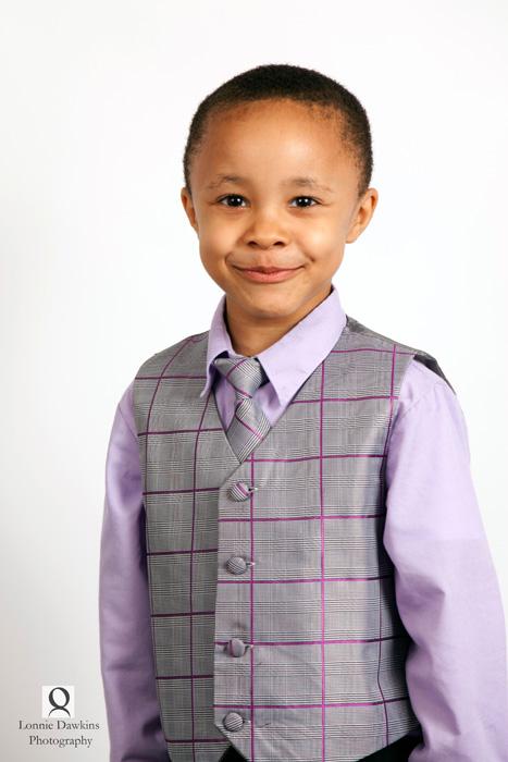 young boy in vest smiling purple tones