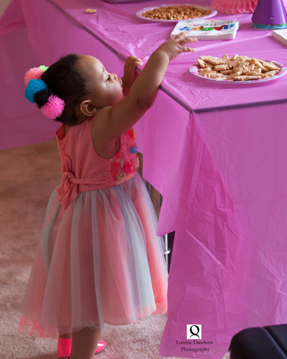 little girl reaching for cookies on table