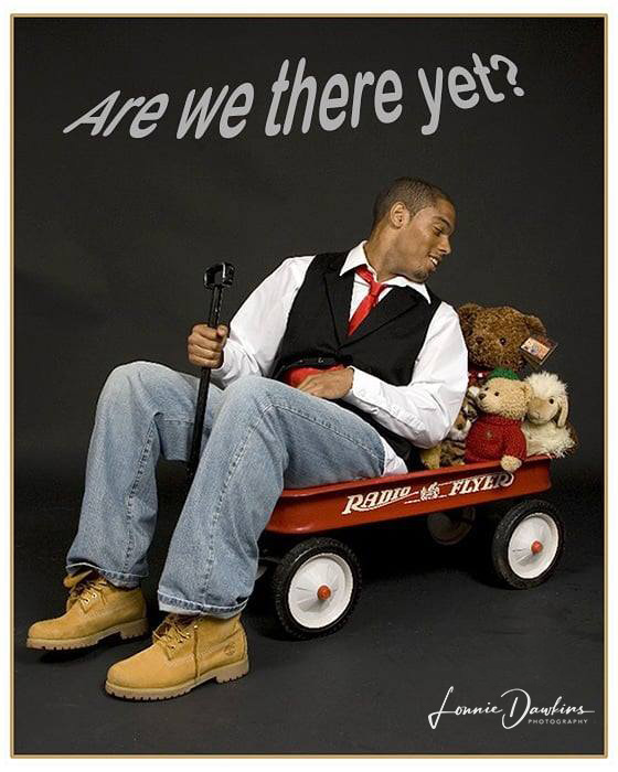 Man in little red wagon filled with stuffed animals