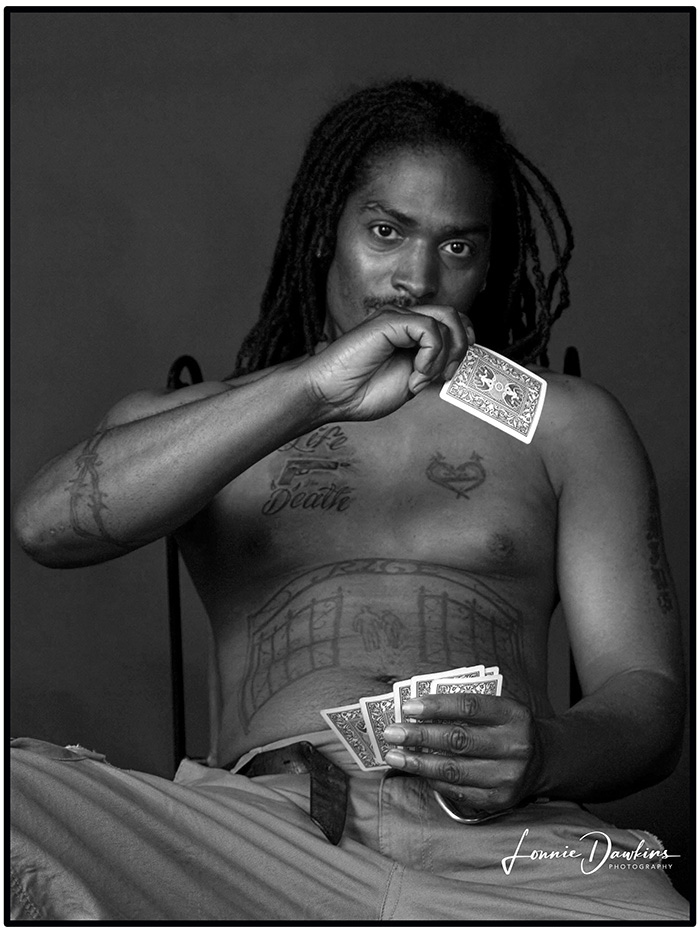 black man with tattoos and dreads playing cards