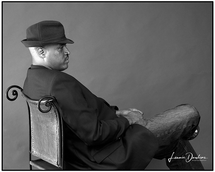 black man with hat in chair wearing jeans and sports coat
